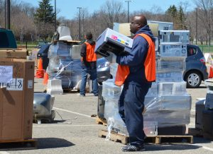 man carrying computer at recycling collections event