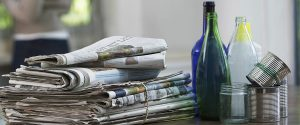 newspapers, glass bottles, and aluminum can sitting on table