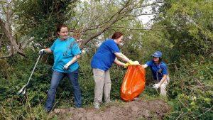 Three volunteers picking up litter during a Great American Cleanup event