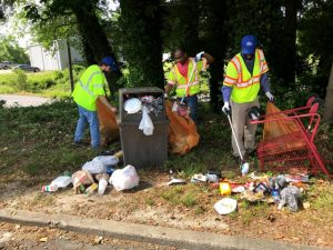 Three volunteers in reflective vests picking up litter in Suffolk for a Great American Cleanup event
