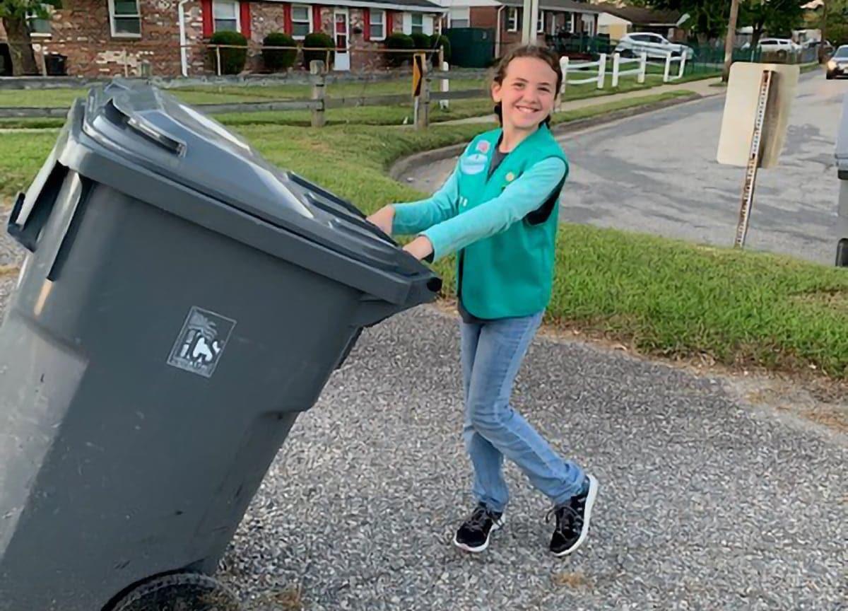 A happy student pushing a trash bin