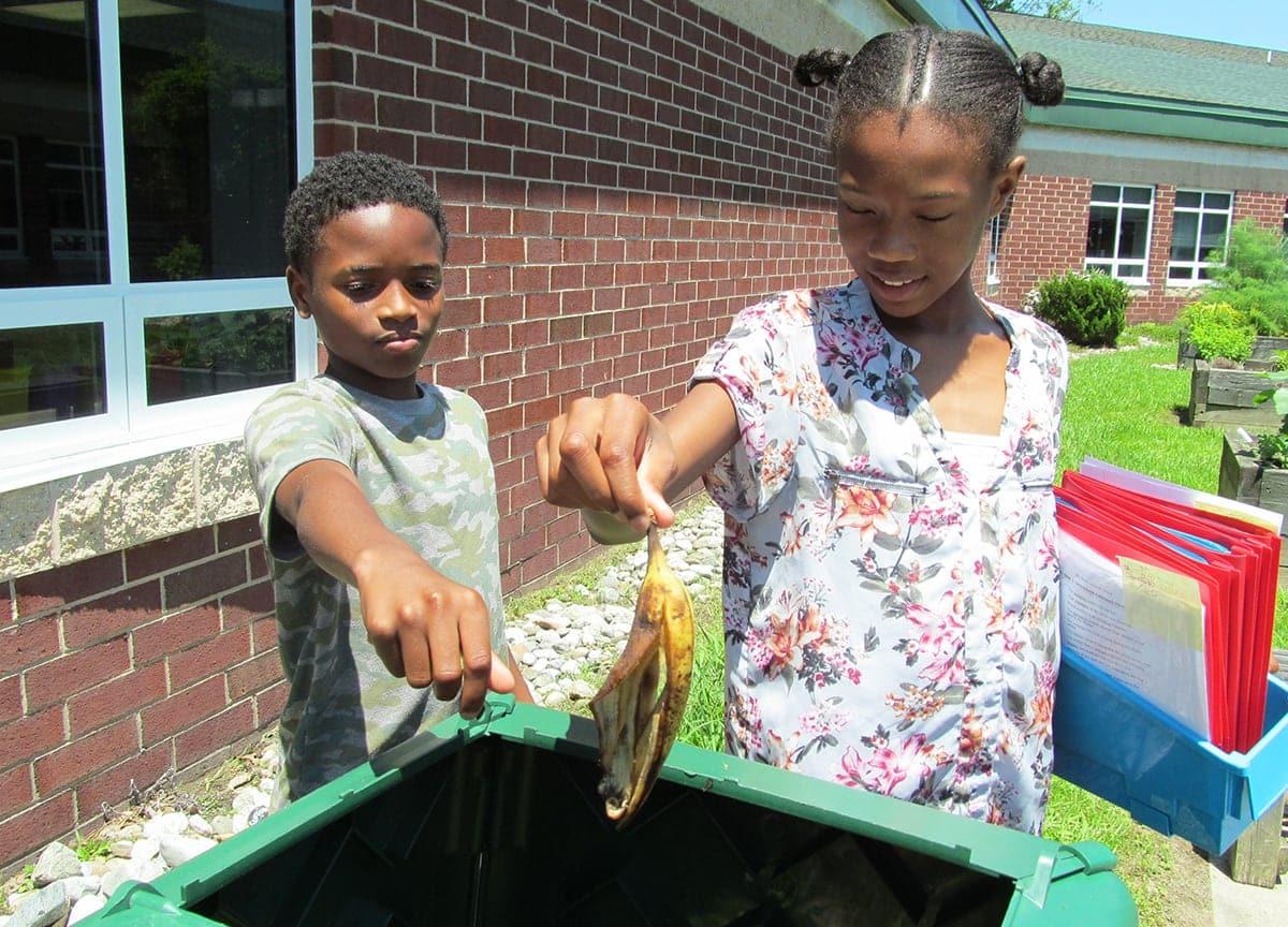 two children throwing away litter
