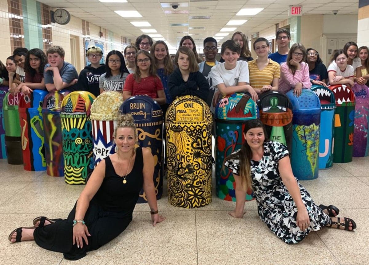 Class of students showing off their painted trashcans